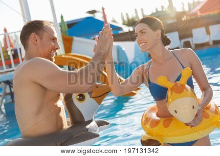 Team work. Lovely joyful young couple in animal-shaped swim rings standing in the swimming pool and giving each other a high five while smiling happily