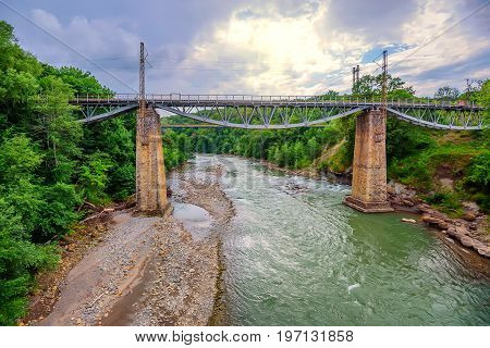 Railroad bridge in summer landscape of mountain forest