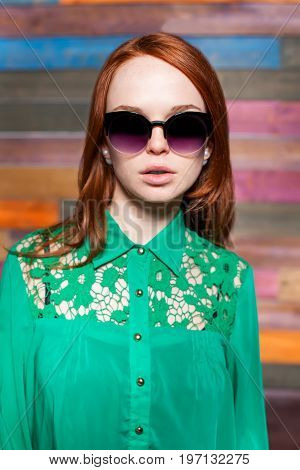attractive redhead girl in greem blouse and sunglasses over color wooden background. beauty model woman with luxurious red hair. hairstyle