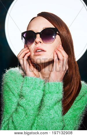 young redhead teen in greem pullover and sunglasses over dark blue background. beauty model woman with luxurious red hair. hairstyle. holiday makeup