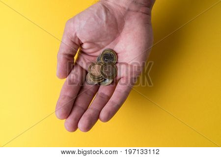A man's palm with coins. Lack of money. Low wages.