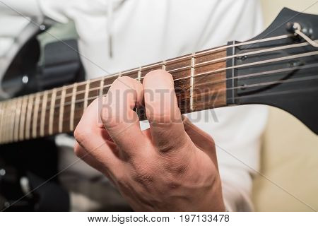 Close-up image of man playing electric guitar
