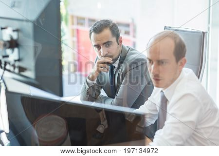 Image of two thoughtful businessmen looking at data on computer screens, solving business issue at business meeting in moder office.