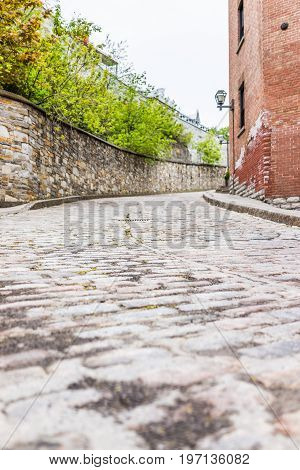 Lower Old Town Narrow Street With Cobblestone Road On Incline Uphill And Residential Brick House And