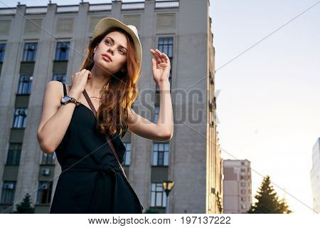 Young beautiful woman in a hat walking along the street in the city, megapolis.