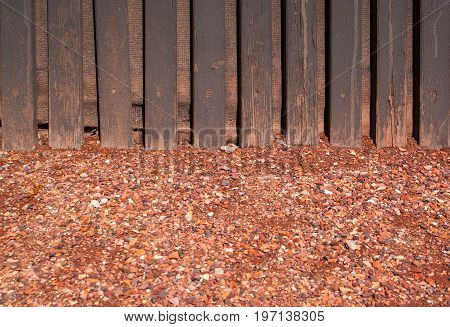 red crushed gravel with wood wall background and texture for graphic design.
