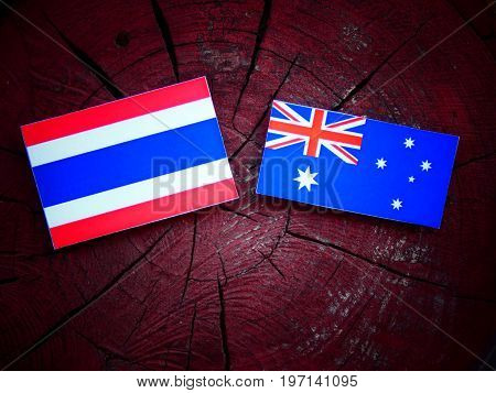 Thai Flag With Australian Flag On A Tree Stump Isolated