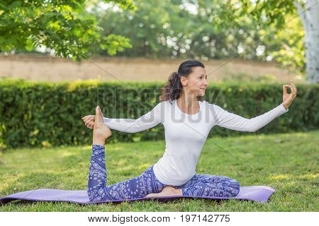 Beautiful young woman training in a park. Fitness in the morning. Relaxation, meditation and balance concept. Pretty girl doing asanas outdoors. Natural background.