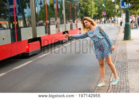 Young woman doing the hitch-hiking in a street of a city Prague, Czech Republic