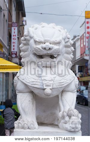 ANTWERP BELGIUM - OCTOBER 2 2016: Statue of a white chinese temple lion in front of the chinese area in antwerp