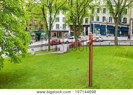 Quebec City Canada - May 30 2017: Montmorency Park National Historic Site with red cross in green grass field and stone wall by old town street called Cote de la Montagne