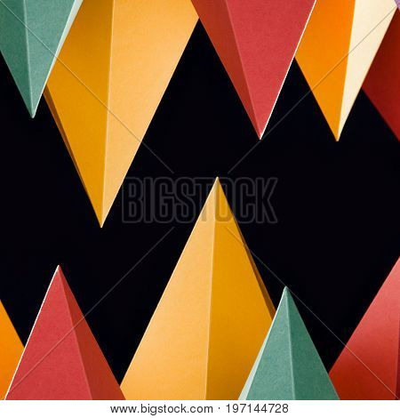 Colorful abstract geometric shapes on black background. Three-dimensional pyramid triangular. Yellow blue pink malachite colored objects. shallow depth field