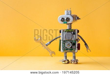 Hand wrench robot serviceman worker on yellow background. Cyborg toy lamp bulb eyes head, electric wires, capacitors vintage resistors