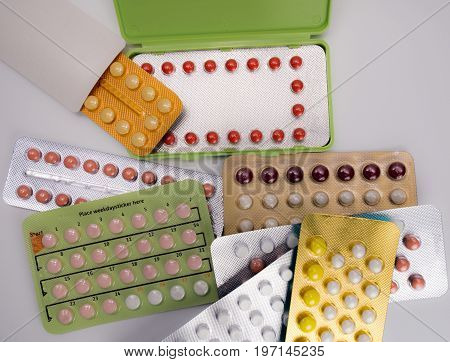 Pile of birth control pills with modern packaging on white background