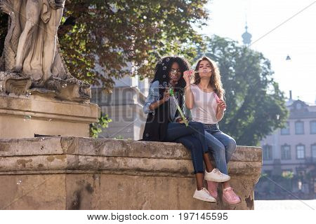 Young and attractive women sitting near the monument in the center of the city and blowing bubbles. Girls wearing jeans and snickers. Casual lifestyle concept.