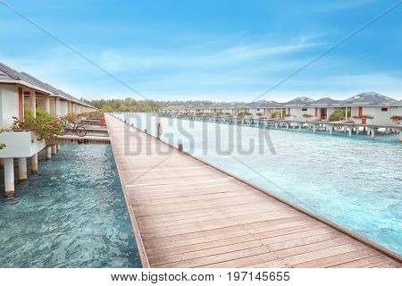View of wooden pontoon and beach houses at sea resort