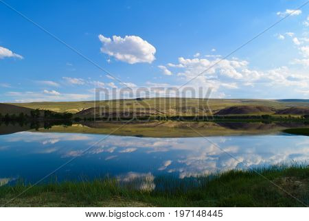 Landscape of calm lake hills green grass and blue sky in Altai mountains. White clouds reflected in water. Chuya steppe Altay Republic Siberia Russia.