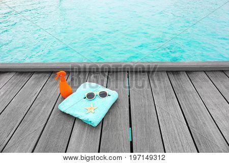 Beach accessories on wooden pontoon at sea resort. Summer vacation concept