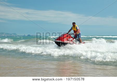 ANAPA, RUSSIA - JUNE 26, 2017: Brutal man with dark hair and short hair, in yellow lifejacket, blue shorts and gray T-shirt skating on red hydrocycle among foamy sea waves on summer sunny day