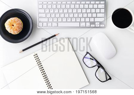 Modern white office desk top table with computer laptop a cup of coffee notebook and other supplies. Top view with copy space on white background. Top view flat lay.