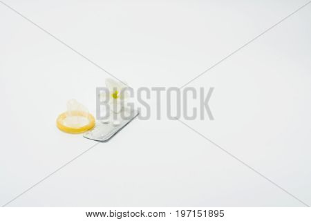 Emergency contraceptive pills with condom and flower on white background