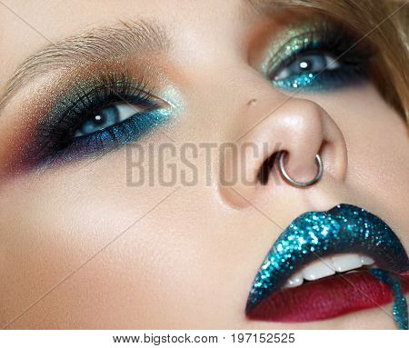 Beautiful young model with fashion colorful make up, perfect skin. Blue brilliant lips. Art make up