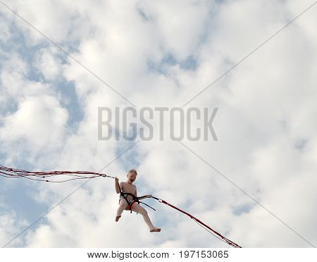 ANAPA, RUSSIA - JUNE 25, 2017: Beach entertainment. Joyful boy with blond hair flies on an air attraction on background of cloudy blue sky and screams with pleasure, wide open mouth