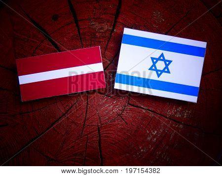 Latvian Flag With Israeli Flag On A Tree Stump Isolated