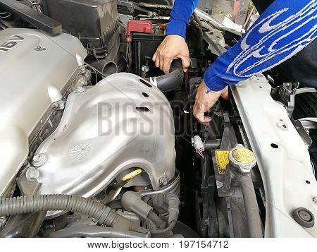 Hands of car mechanic in auto repair service on Metal background