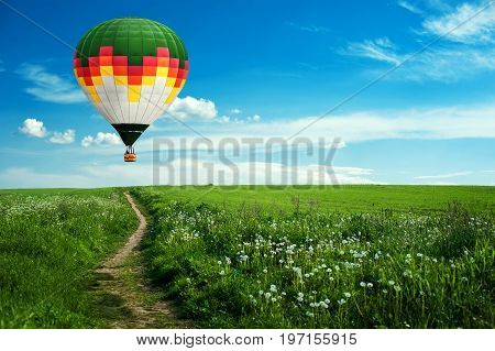Colorful hot-air balloon flying over the field against blue cloudy sky