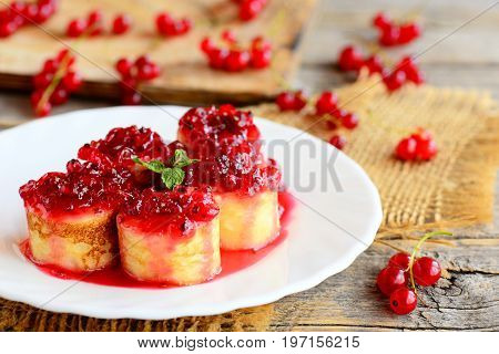 Fried pancakes with redcurrant sauce. Homemade pancakes sushi on a white plate and a vintage wooden table. Beautiful and healthy breakfast for kids and whole family