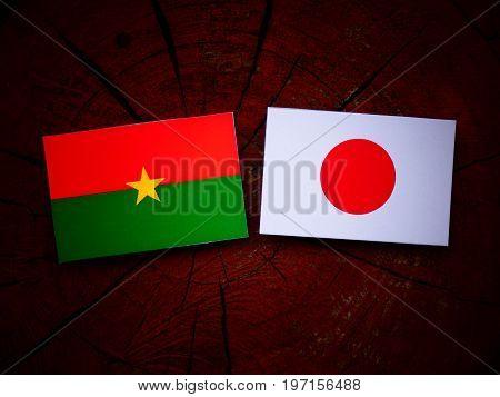 Burkina Faso Flag With Japanese Flag On A Tree Stump Isolated
