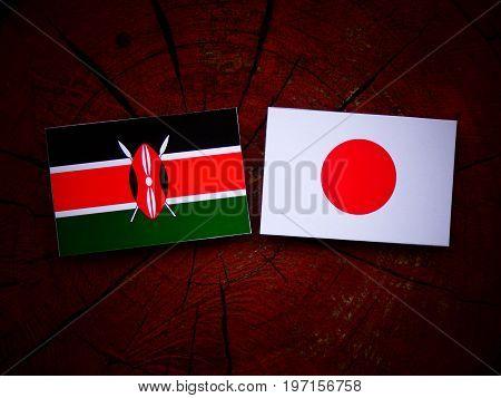 Kenyan Flag With Japanese Flag On A Tree Stump Isolated