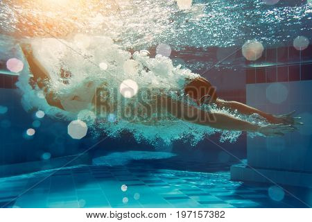 Man is jumping into the swimming pool. Man is swimming under water in swimming pool.
