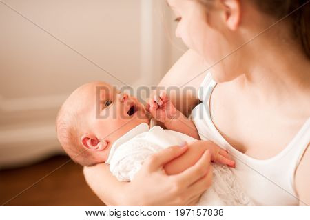 Smiling mother holding small infant baby indoors. Looking at each other. Maternity. Motherhood. Family time.