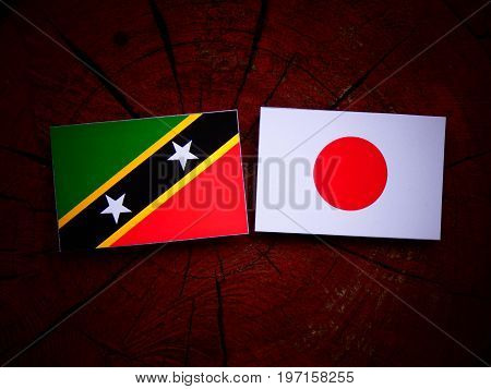 Saint Kitts And Nevis Flag With Japanese Flag On A Tree Stump Isolated
