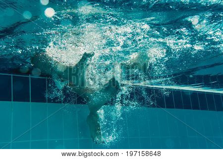 Underwater view of couple legs in the swimming pool. Making bubbles.