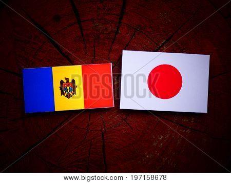 Moldovan Flag With Japanese Flag On A Tree Stump Isolated