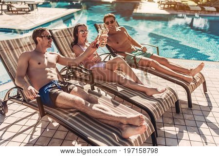 Group of young friends is lying on a chaise-longues near swimming pool and smiling. Having rest and drinking beer together.