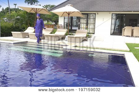 attractive woman in a Muslim swimwear burkini goes to the pool in a tropical garden