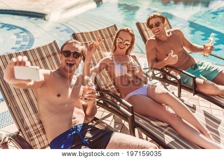 Group of young friends is lying on a chaise-longues near swimming pool and smiling while taking selfie on a smart phone. Having rest together and drinking beer.