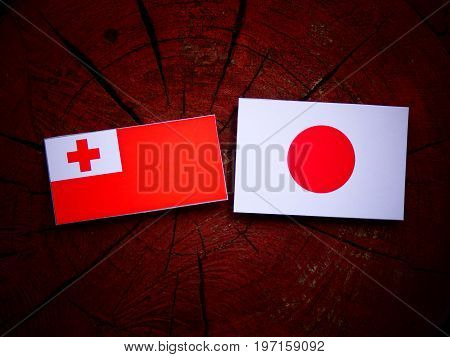 Tongan Flag With Japanese Flag On A Tree Stump Isolated