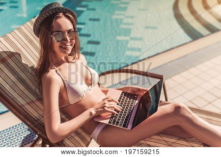 Working even on vacation! Attractive young woman and hat is lying on a chaise-longue near swimming pool with laptop.