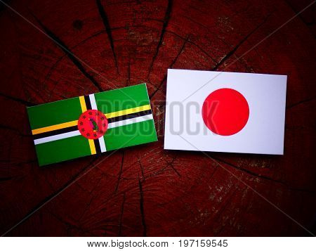 Dominica Flag With Japanese Flag On A Tree Stump Isolated