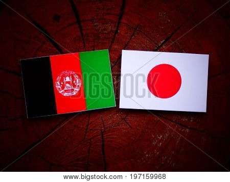 Afghani Flag With Japanese Flag On A Tree Stump Isolated