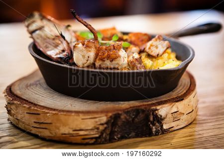 Pulpo a la gallega. Boiled octopus, baked in a frying pan in a coal stove with potatoes