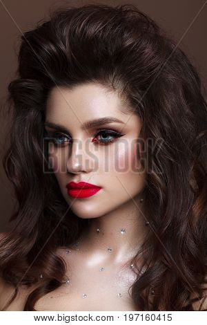 Beautiful young model with professional make up, perfect skin, volume hairdo. Red lips.