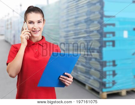 Young worker with clipboard talking on phone at storehouse. Wholesale and logistic concept