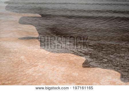 Oil spill on water near shore. Concept of ecological disaster