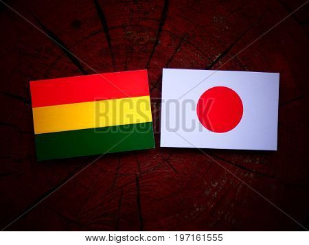 Bolivian Flag With Japanese Flag On A Tree Stump Isolated
